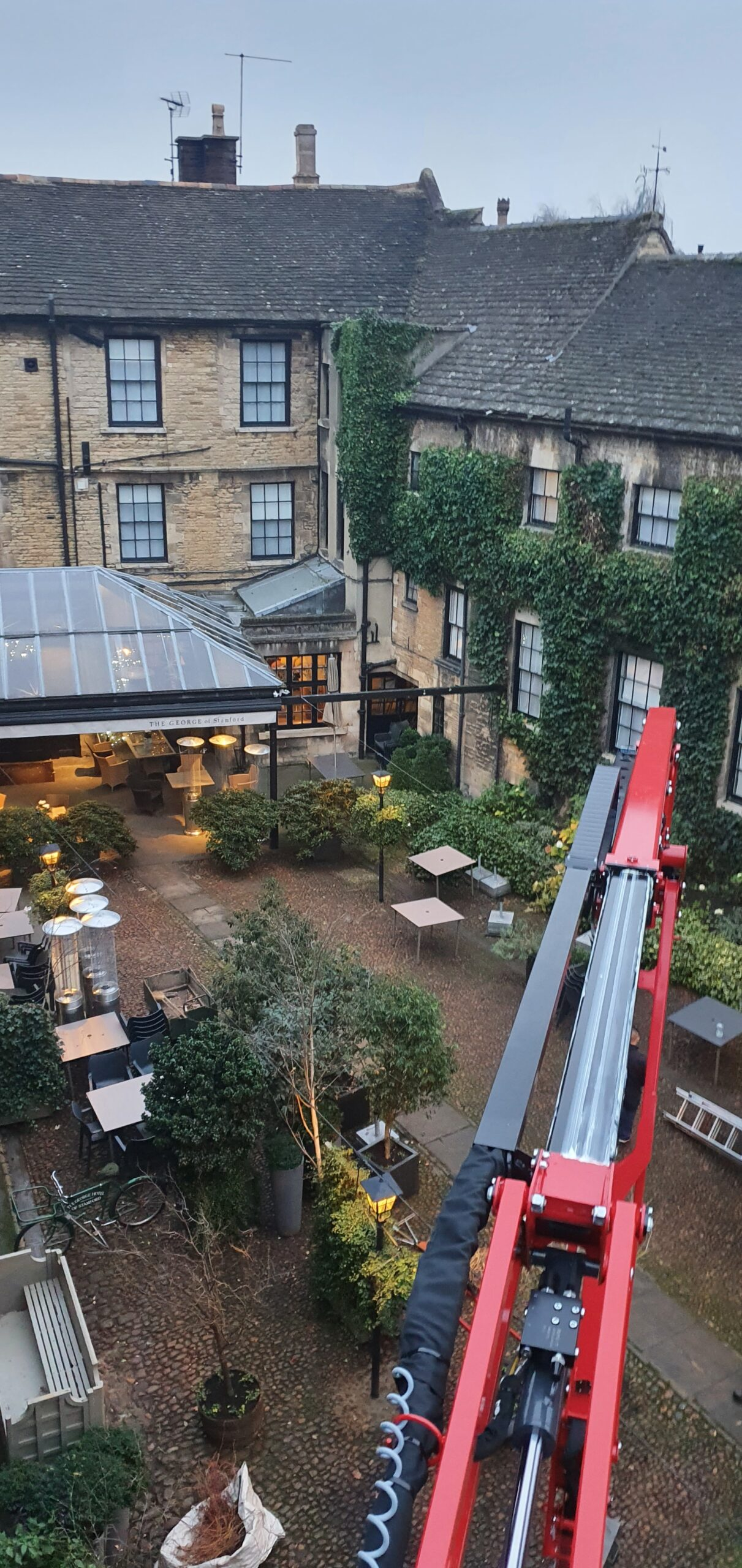 17m Hinowa 17.75m spiderlift trimming ivy in the courtyard of The George of Stamford - Access platfrom hire from Warren Access