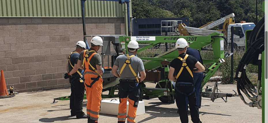 IPAF Training with trainees wearing safety harnesses - always wear a harness when operating a boom lift.